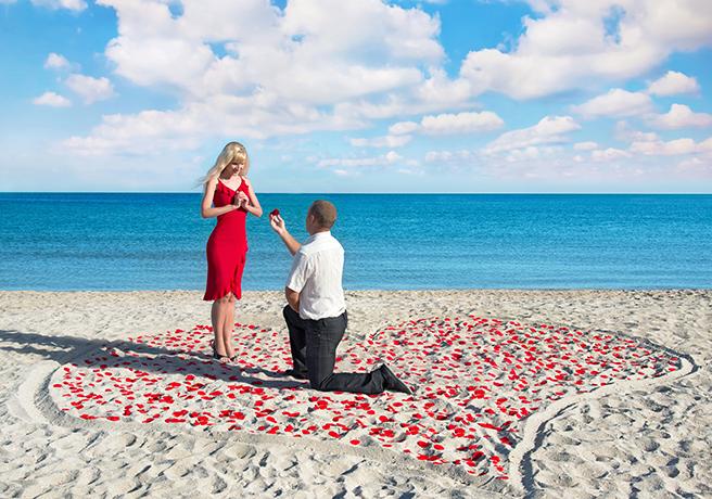 海辺でプロポーズをするカップル