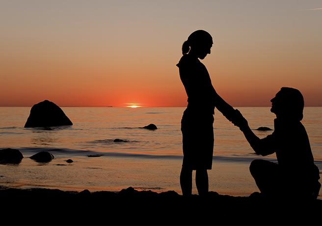 夕方の浜辺でプロポーズするカップル