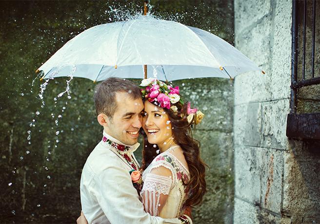 雨の日の結婚式で相合傘を差して撮影する新郎新婦