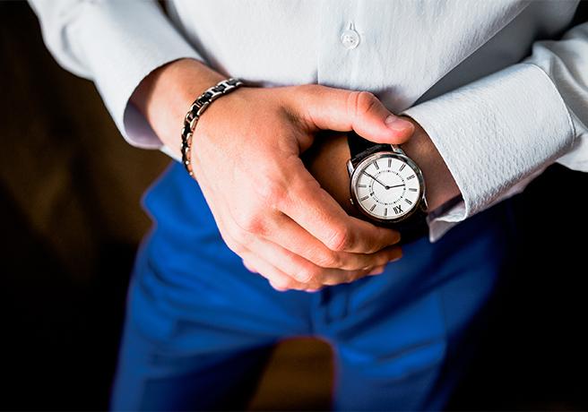 腕時計を着けた手を押さえるスーツ姿の男性