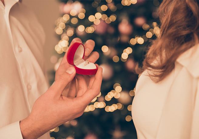 クリスマスツリーの前でパートナーに婚約指輪を渡す男性