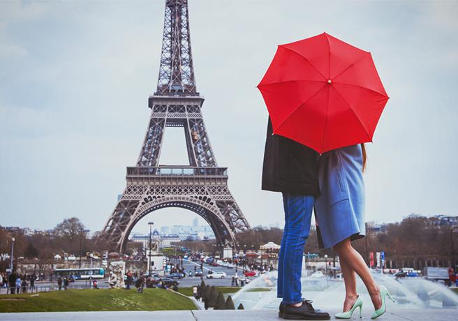 エッフェル塔の前で傘をさしながら抱き合うカップル