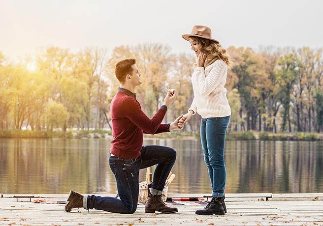 池の前で箱パカプロポーズをする男性