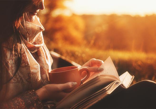 秋に屋外で読書する女性