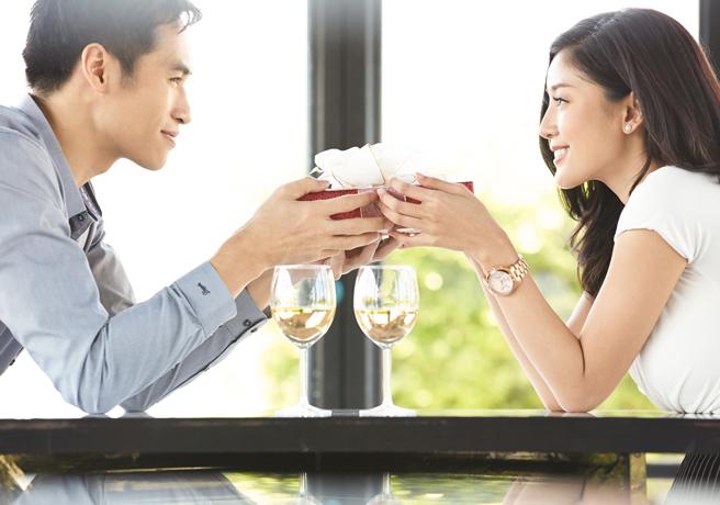 レストランでプロポーズをする男性とプレゼントを受け取る女性