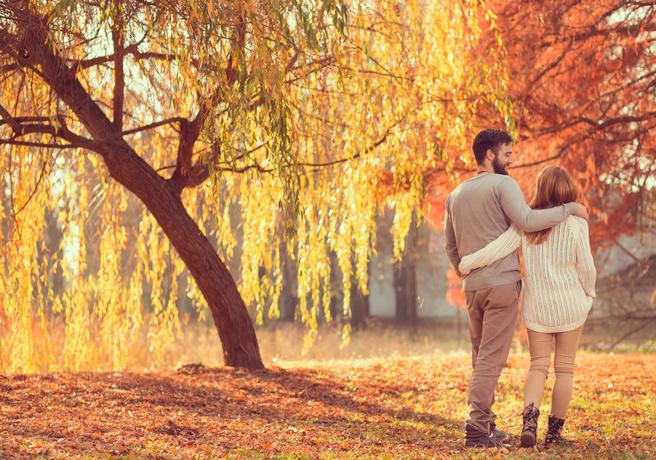紅葉した木々の中を歩くカップル