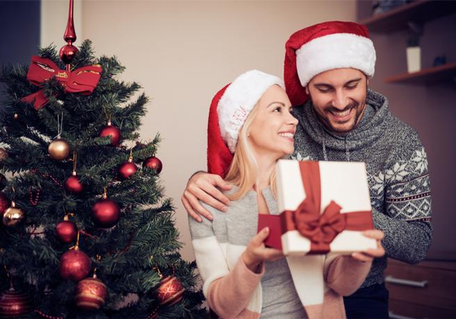 ツリーの前でクリスマスプレゼントを開けるカップル