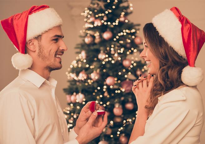 ツリーの前でプロポーズする男性と喜ぶ女性