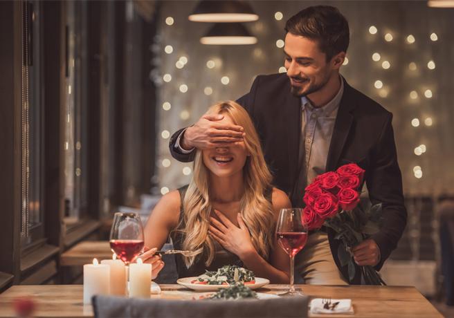 レストランでサプライズプロポーズをする男性と受ける女性
