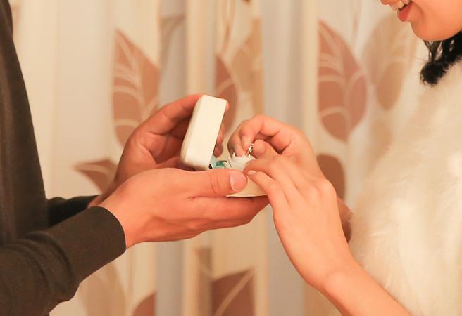 部屋でプロポーズをする男性と指輪を引き抜く女性